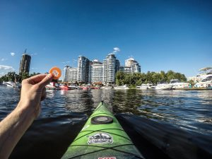 person holding green kayak on water near city buildings during daytime