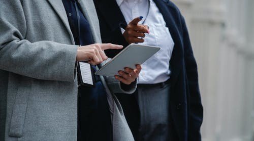 Anonymous multiethnic coworkers browsing tablet on street