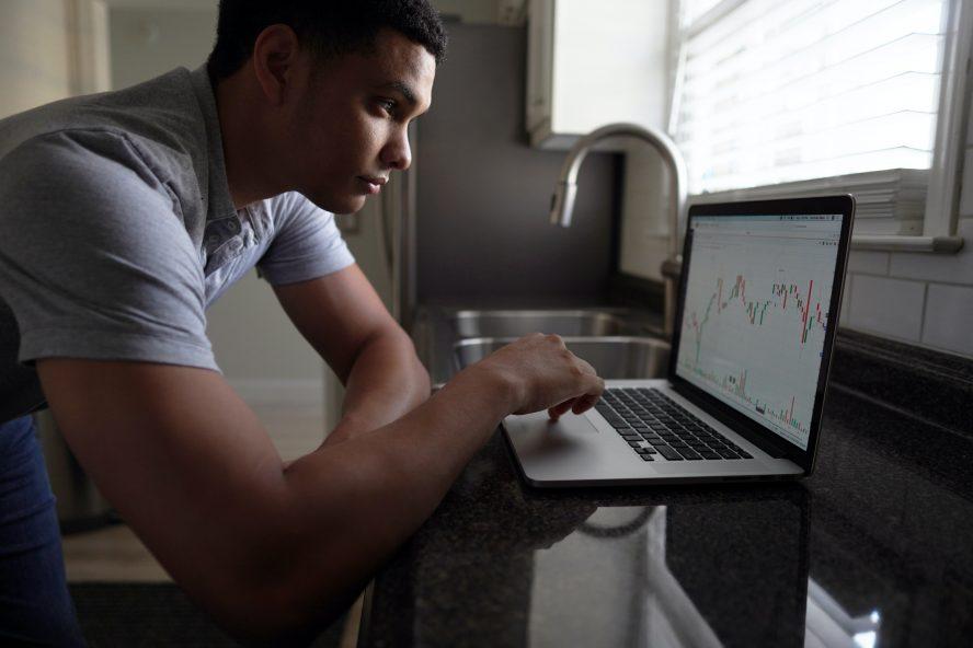 man in gray t-shirt using macbook pro