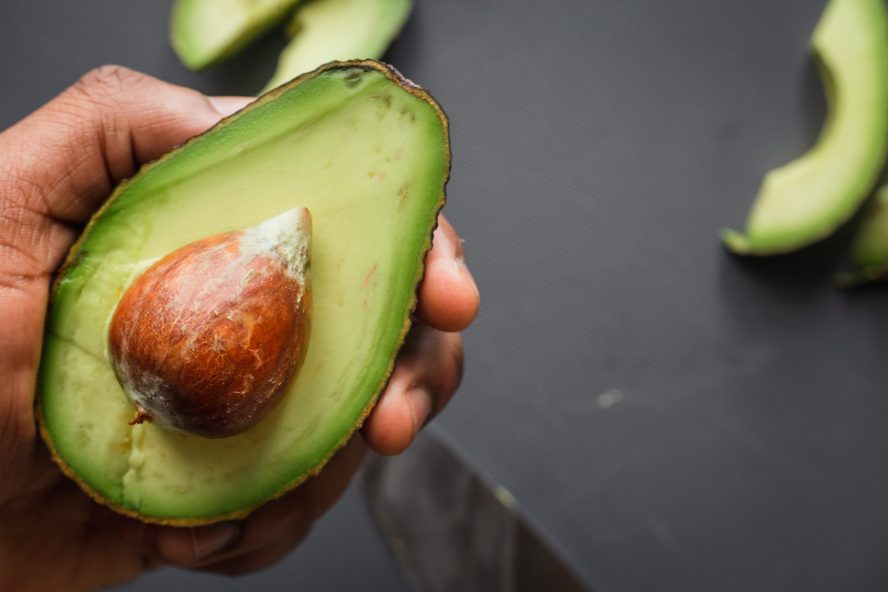 person holding green and brown sliced fruit