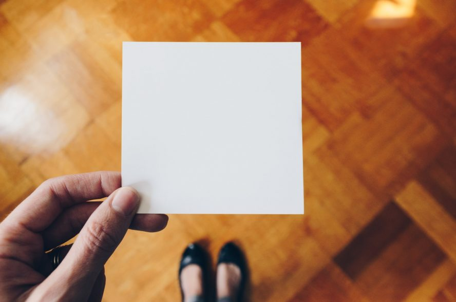 person holding white paper over brown wooden floor