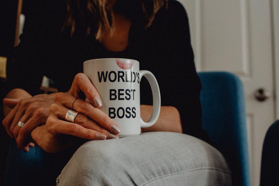 woman in black long sleeve shirt holding white ceramic mug